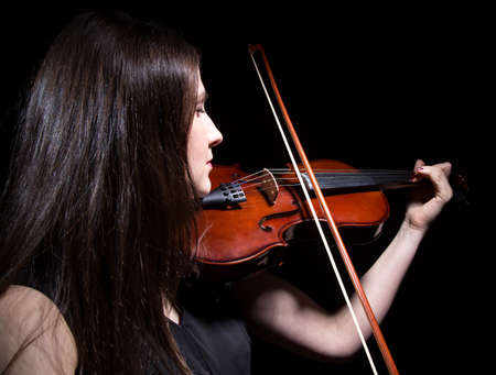 fiddles: Woman playing on violin from back on black background