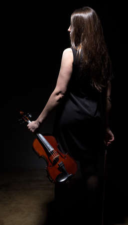 fiddles: Brunette woman with violin from back on black background Stock Photo