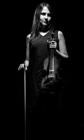 fiddlestick: Black and white photo of woman with violin on black background