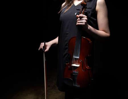 fiddlestick: Woman holding violin and fiddlestick on black background Stock Photo