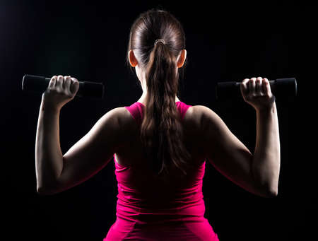 exertion: Coach holds the weights on black background