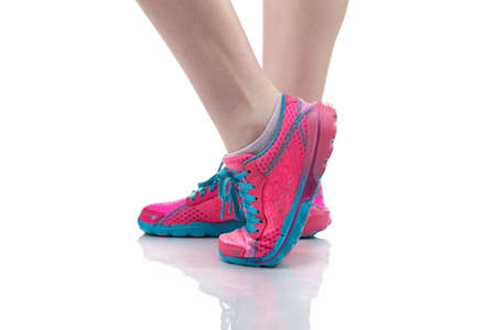 exertion: Womans feet in pink sneakers on white background
