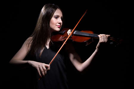 fiddle: Smiling woman playing on fiddle on black background Stock Photo