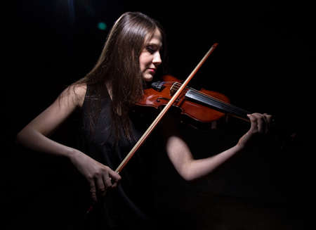 fiddles: Young woman playing on violin on black background