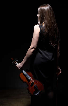 fiddlestick: Brunette woman with fiddle from back on black background Stock Photo