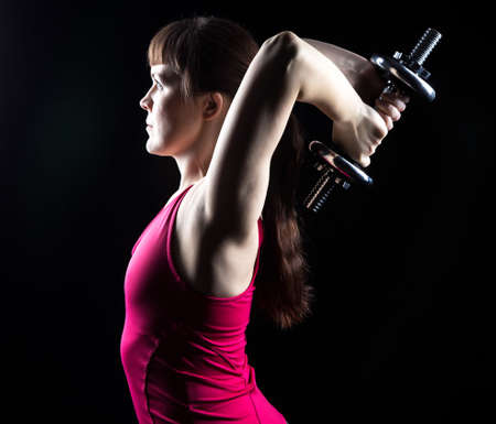 deflection: Woman doing exercise with weights on black background Stock Photo