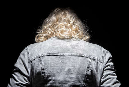 leaned: Womans leaned head and jeans jacket on black background