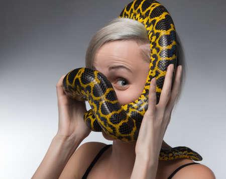 Blond woman and strangling yellow anaconda Stock Photo