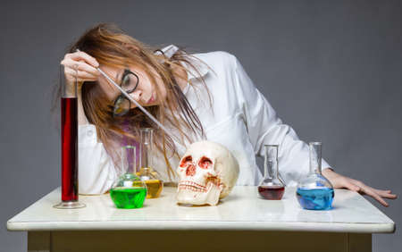 Working chemist with human skull Stock Photo