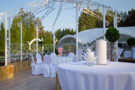 Photo of empty wedding table with white tablecloth