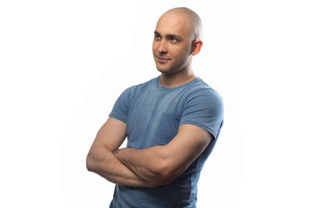Photo of the adult bald man with arms crossed