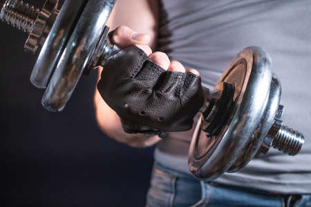 Strong man in sporty gloves with dumbbell