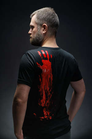Photo of man with red handprint on t-shirt
