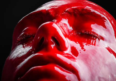 Photo of woman's face with draining red paint, close-up