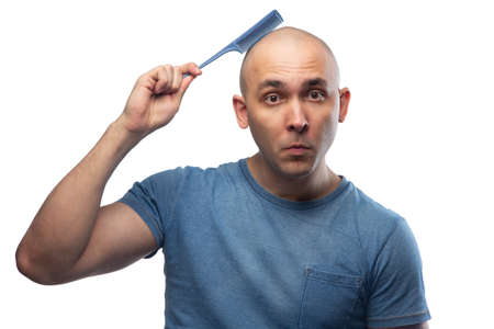 Photo of confused bald man in blue tee shirt with hairbrush