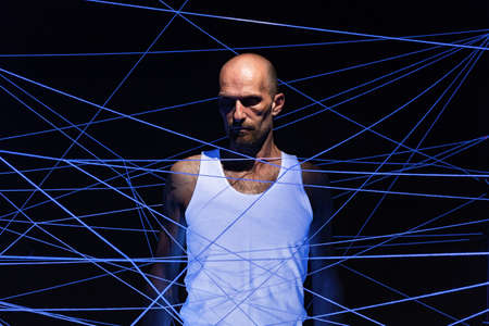 Photo of adult man tangled in white threads in neon light