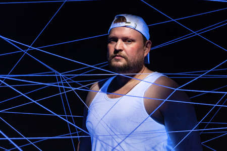 Portrait of fat man tangled in white threads in ultraviolet