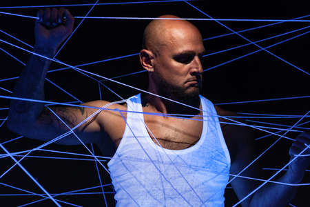 Image of bald man tangled in white threads