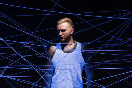 Photo of bearded man tangled in white threads in ultraviolet