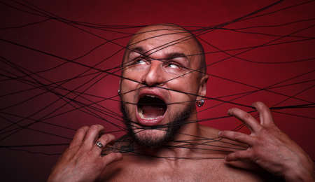 Portrait of tangled in threads bald screaming man