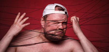 Photo of tangled in black threads man on red background