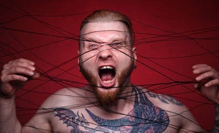 Image of tangled in black threads bearded screaming man