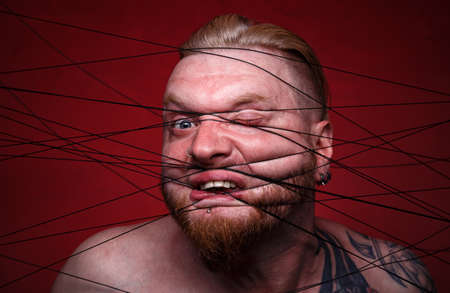 Portrait of tangled in black threads blond man on red background