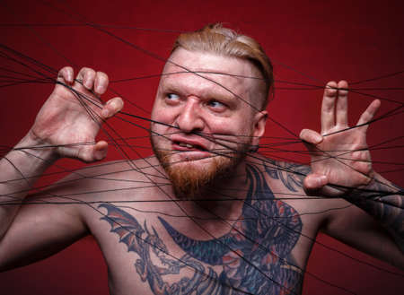 Image of tangled in threads bearded mad man on red background Stock fotó