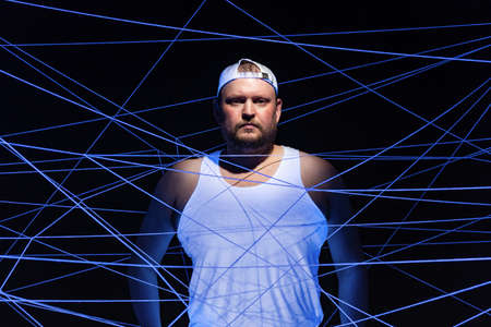 Portrait of fat man tangled in threads in neon light
