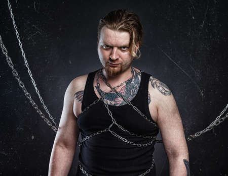 Photo of a tattooed young blond man bound in chains Stock Photo