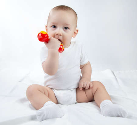 Image of a nine-month-old baby with rattle on a white background