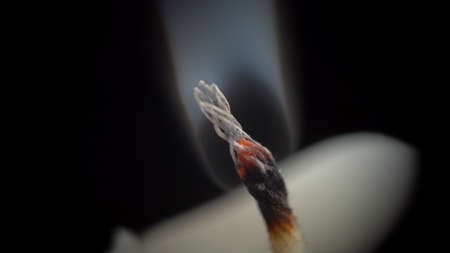 Picture of smouldering candle on black background