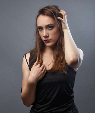 Image of woman touching her hair with purple lips on grey background