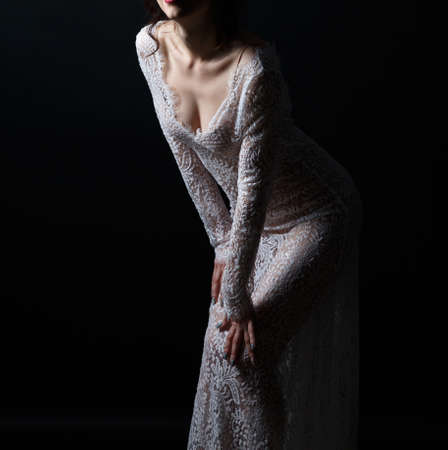 Young woman in see-through dress on dark background