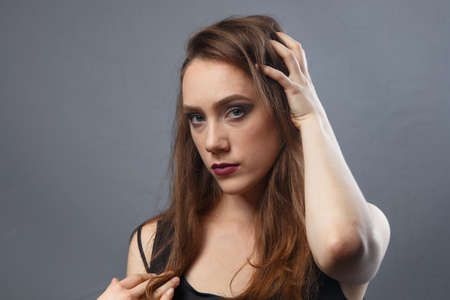 Photo of girl touching her hair with purple lips on grey background