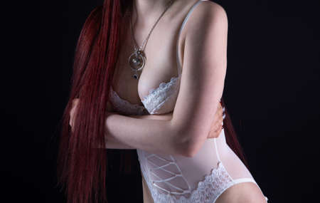 Image of young woman in white lingerie with arms crossed