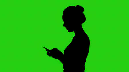 Teens silhouette with smartphone on green background