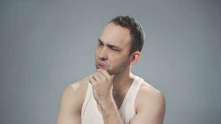 Photo of thinking bristly man on gray background