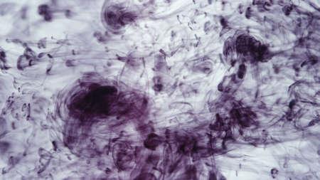 Image of drops of purple ink falling in water Фото со стока