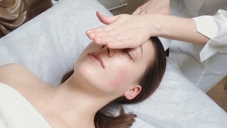 Brunette woman gets a facial massage course in salon