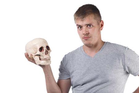 Photo of puzzled man holding human skull Reklamní fotografie
