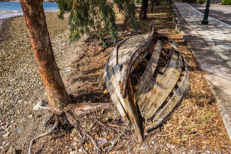 water s edge: an old destroyed boat on the beach in grecce