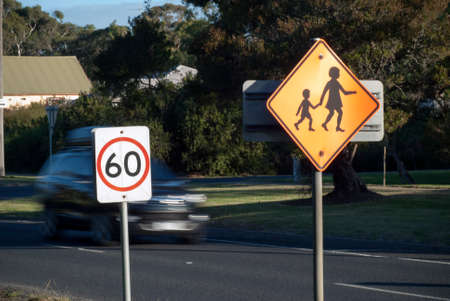 sixty: car speeding behind sixty speed limit sign Stock Photo