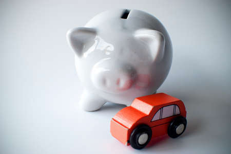 sales bank: piggy bank behind car for saving or for a loan Stock Photo