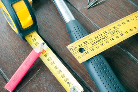 t square: hammer, ruler tape measure, pencil and nails on timber background Stock Photo