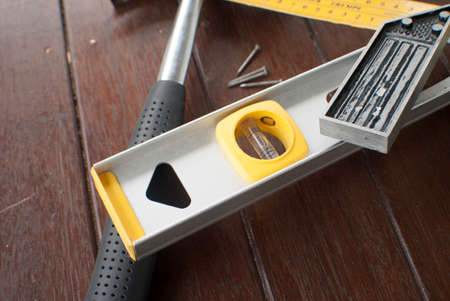 square ruler: hammer, level, t square ruler and nails on timber background