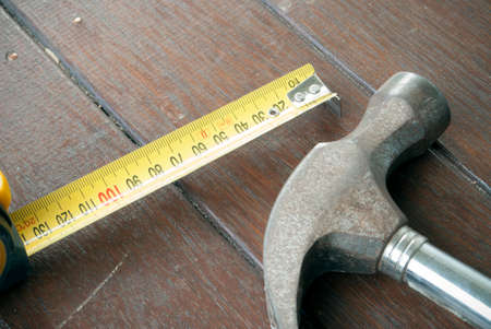claw hammer: tape measure and claw hammer on timber background