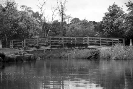 bridge over water: black and white photo of a wooden timber bridge over water