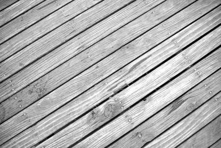 timbering: angled ground view of textured timber boardwalk in black and white