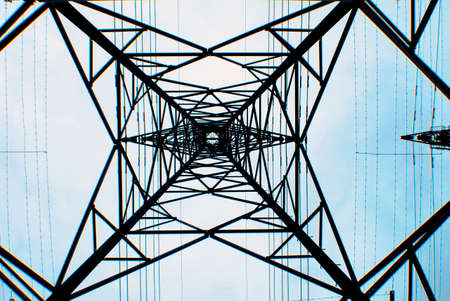light transmission: looking upwards at the base a transmission tower with a light blue sky background